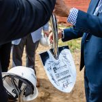 A reflective shovel being handed to Mayor Hancock of Denver