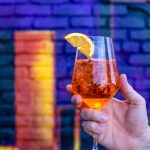 A hand holding a cocktail in front of a brick wall