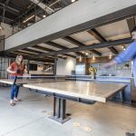 Two people playing ping-pong in an office lounge