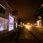 A dark street in RiNo with a colorful projection on a garage door