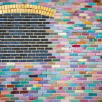 A brick wall that has been painted with bright colors