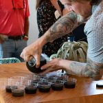 A tattooed man pouring homemade juice into plastic cups