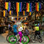 Brightly colored bicyclists viewing Larimer Square during Pride Week