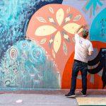 An image of a man creating a street art mural