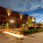 A dusk image of Platte Street Plaza with lights on