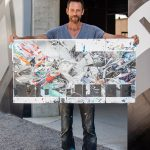 An artist holding up a scaled down version of his street art mural