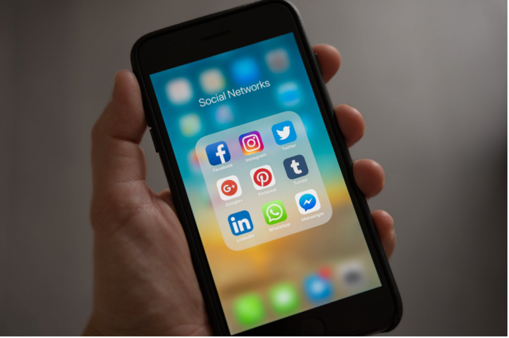 using social media for SEO - a person holidng a phone with social icons showing